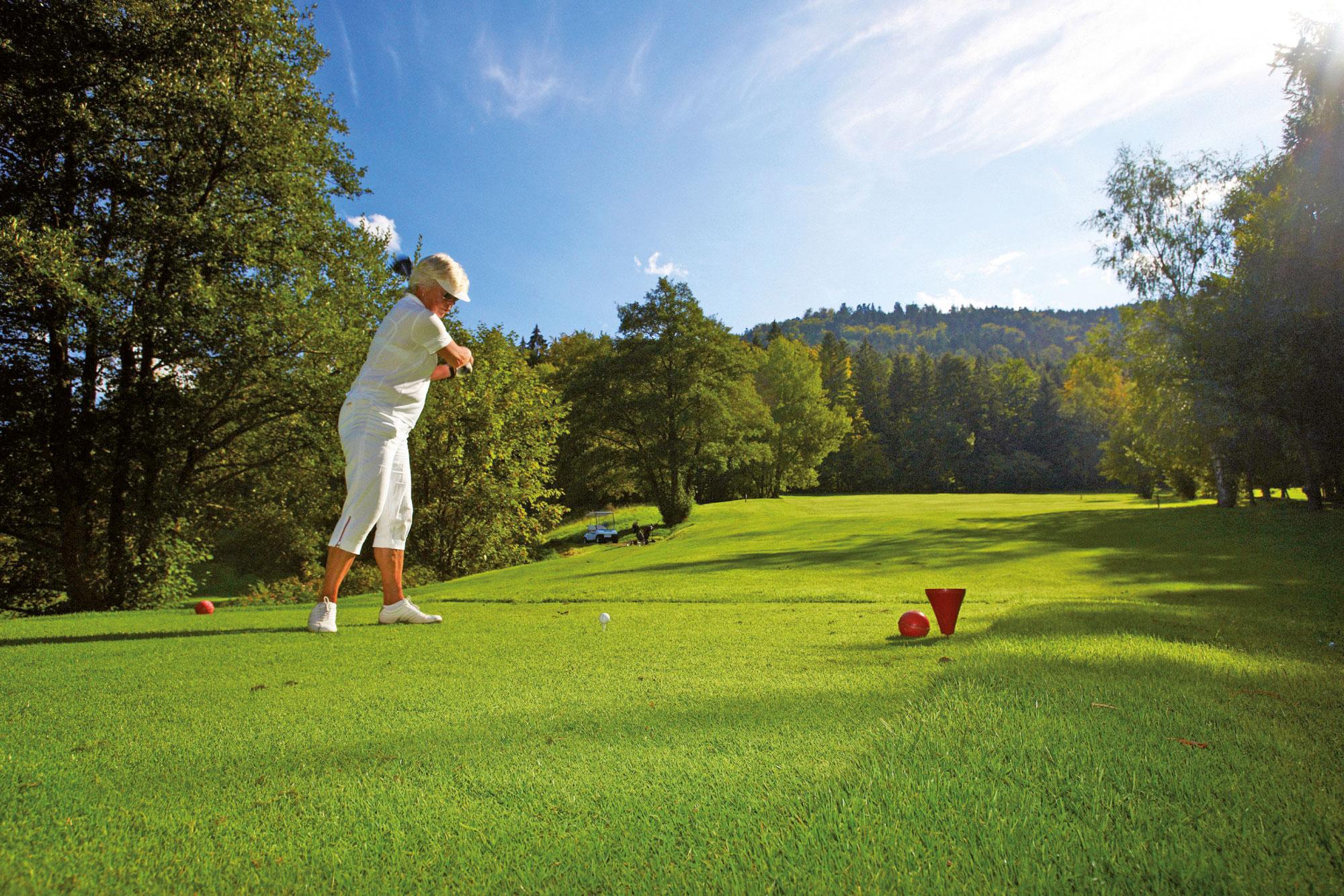 Frau beim Golfen auf dem Golfplatz