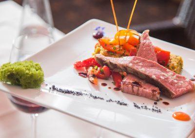 Teller mit liebevoll angerichetem Menü mit zart rosa gebratenem Fleisch und gegrilltem Gemüse