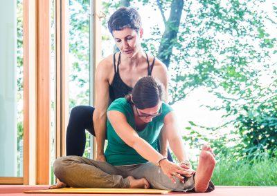 Selfness Leiterin Kerstin Weinbrecht während der Hilfestellung bei einer Yoga Übung mit einem Gast des Schwarzwald Panoramas