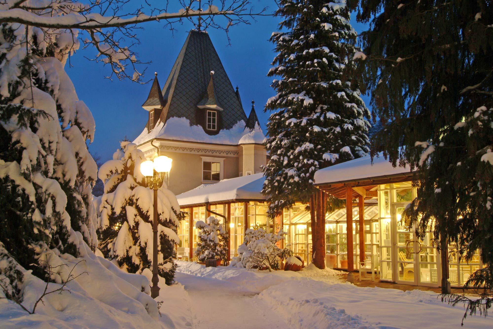 Beleuchtetes Kurhaus von Bad Herrenalb im Winter mit schneebedeckter Landschaft