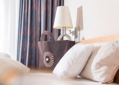 Detailaufnahme vom Bett und einer bedruckten Stofftasche mit dem Logo des Schwarzwald Panoramas
