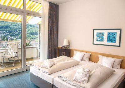 helles Hotelzimmer im Schwarzwald Panorama mit komfortablem Doppelbett und Balkon mit Ausblick auf den Ort und die Landschaft von Bad Herrenalb