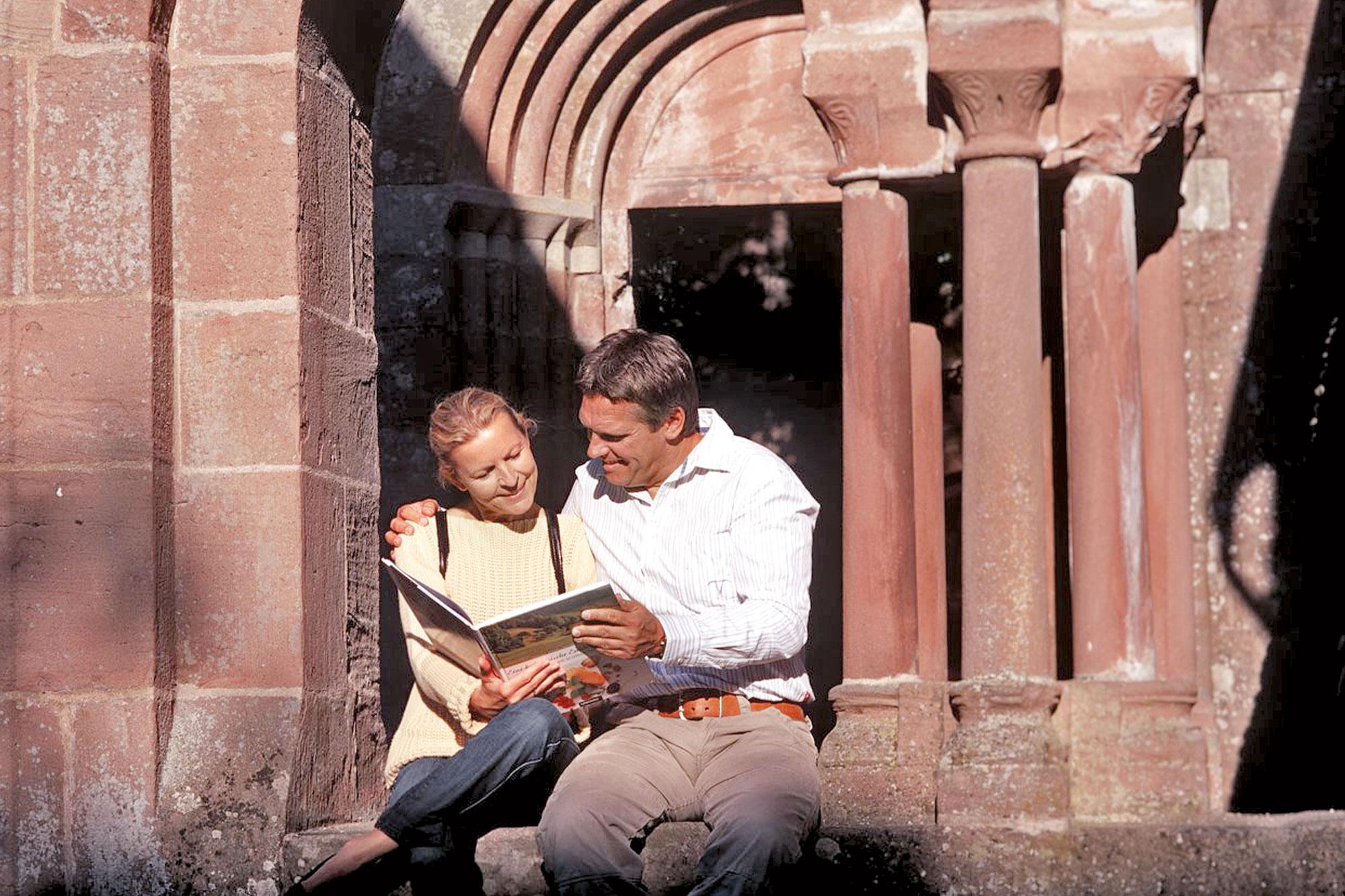Ein Paar sitzt mit einem Buch in der Hand vor einem Kloster