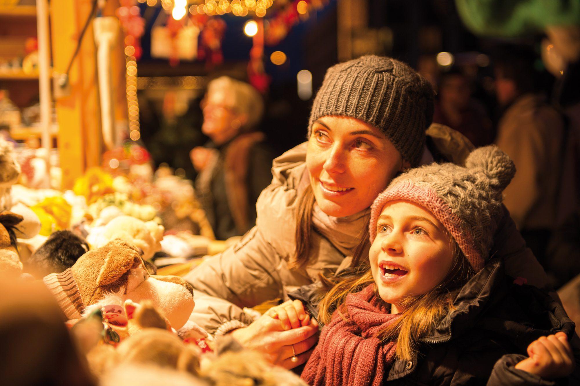 Mutter und Tochter stehen auf einem Weihnachtsmarkt