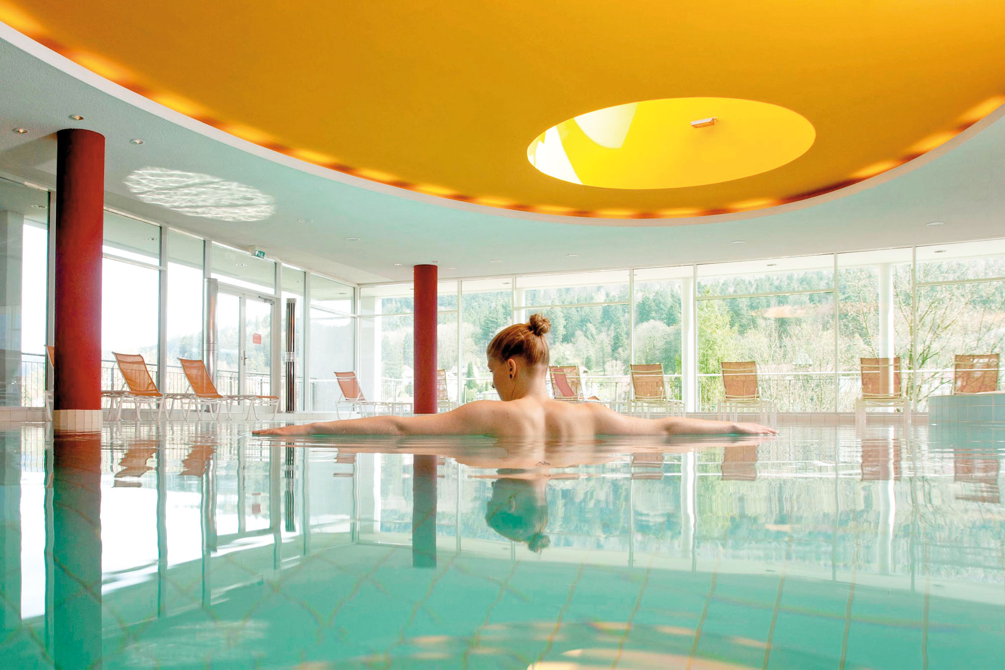 wellness area at wellness hotel Schwarzwald Panorama in Baden Württemberg with indoor pool and panoramic windows with a view of the surrounding landscape