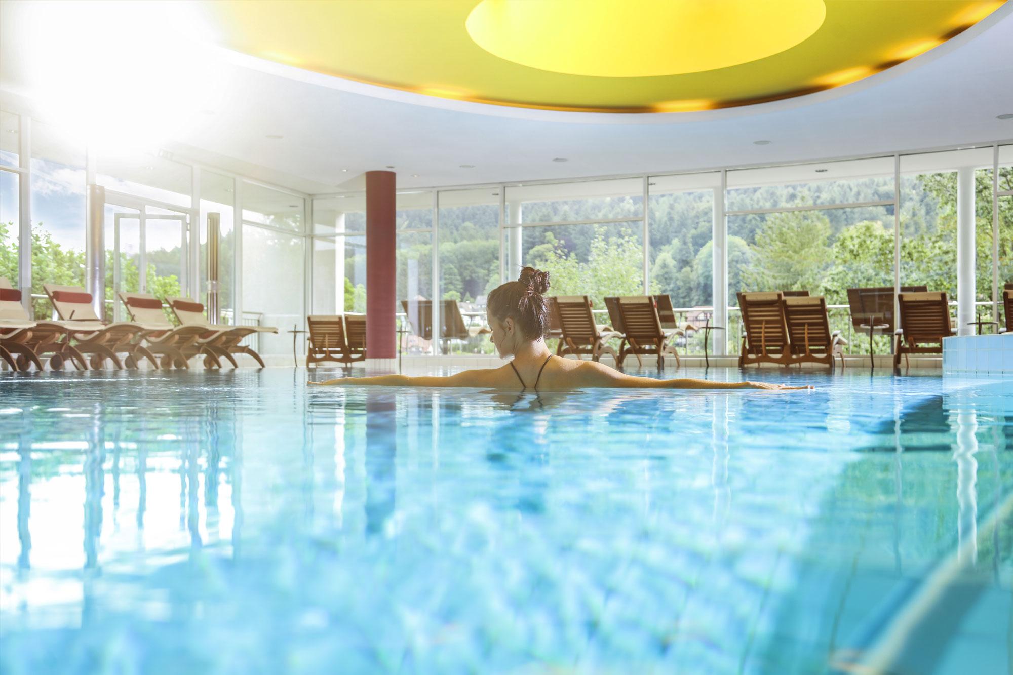 Wellnessbereich im Hotel Schwarzwald Panorama mit Innenpool und Panoramafenstern mit Blick auf die umliegende Landschaft