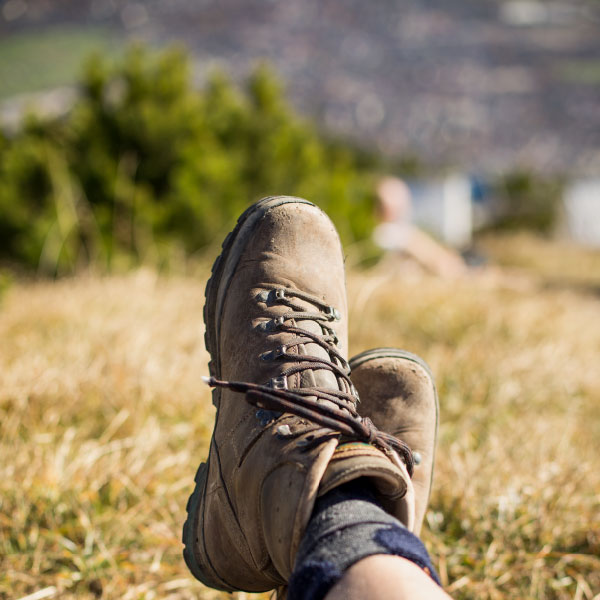 etail of a man with hiking boots lying on a meadow and resting