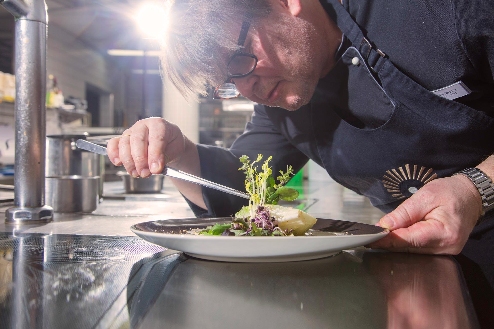 Koch des Schwarzwald Panoramas beim Zubereiten von kulinarischen Häppchen mit frischem Salat und gegrilltem Gemüse in Bio-Qualität
