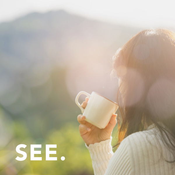 See: Woman with a cup of coffee looks into nature