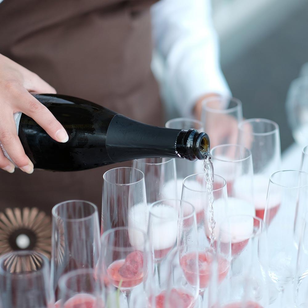 Service-Mitarbeiterin vom Schwarzwald Panorama gießt Champagner in Gläser