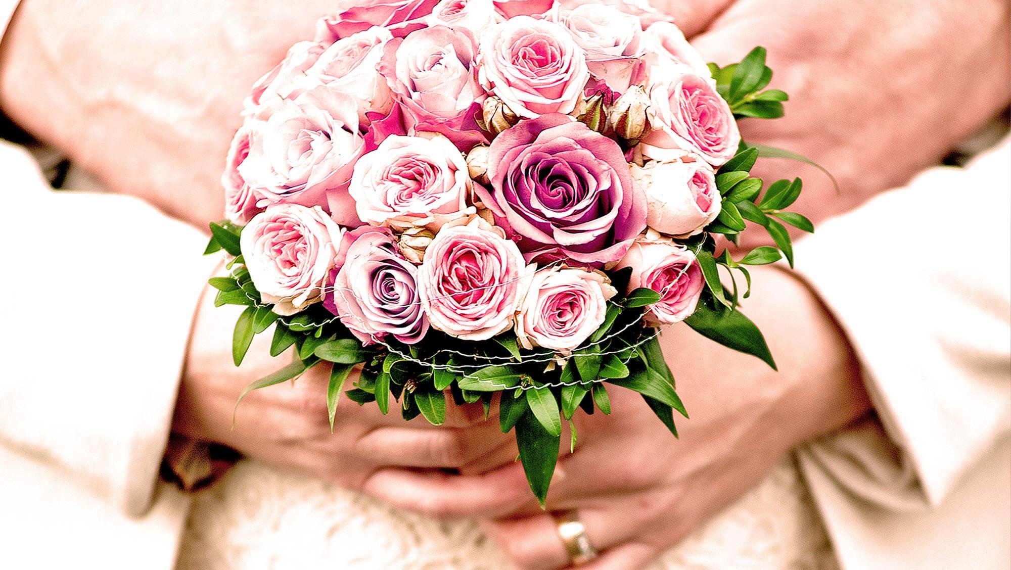 Brautpaar hält zur Hochzeit einen Brautstrauß aus Rosen