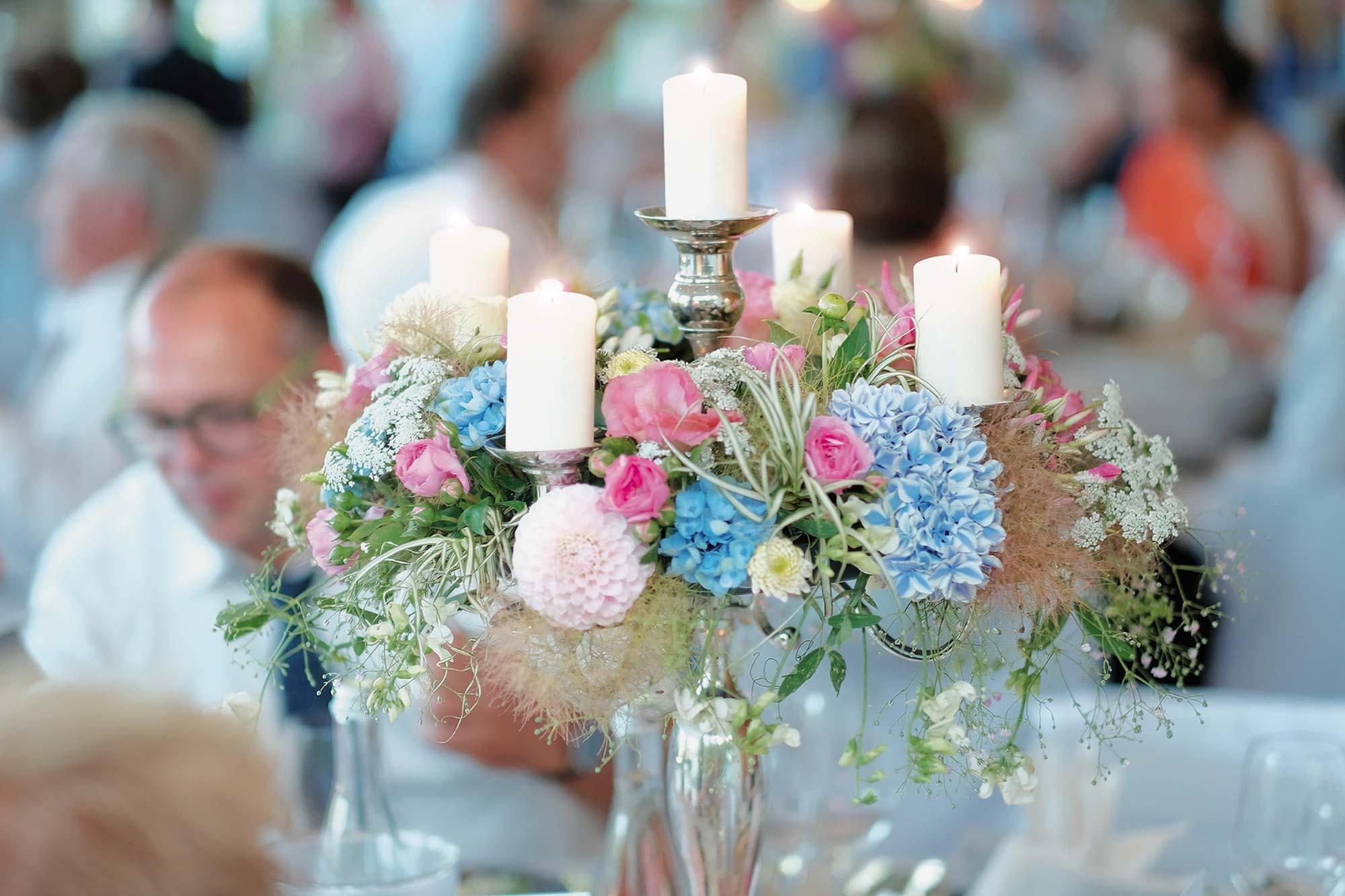 buntes Blumenbouquet auf einem Kerzenständer bei einer Feier im Schwarzwald Panorama