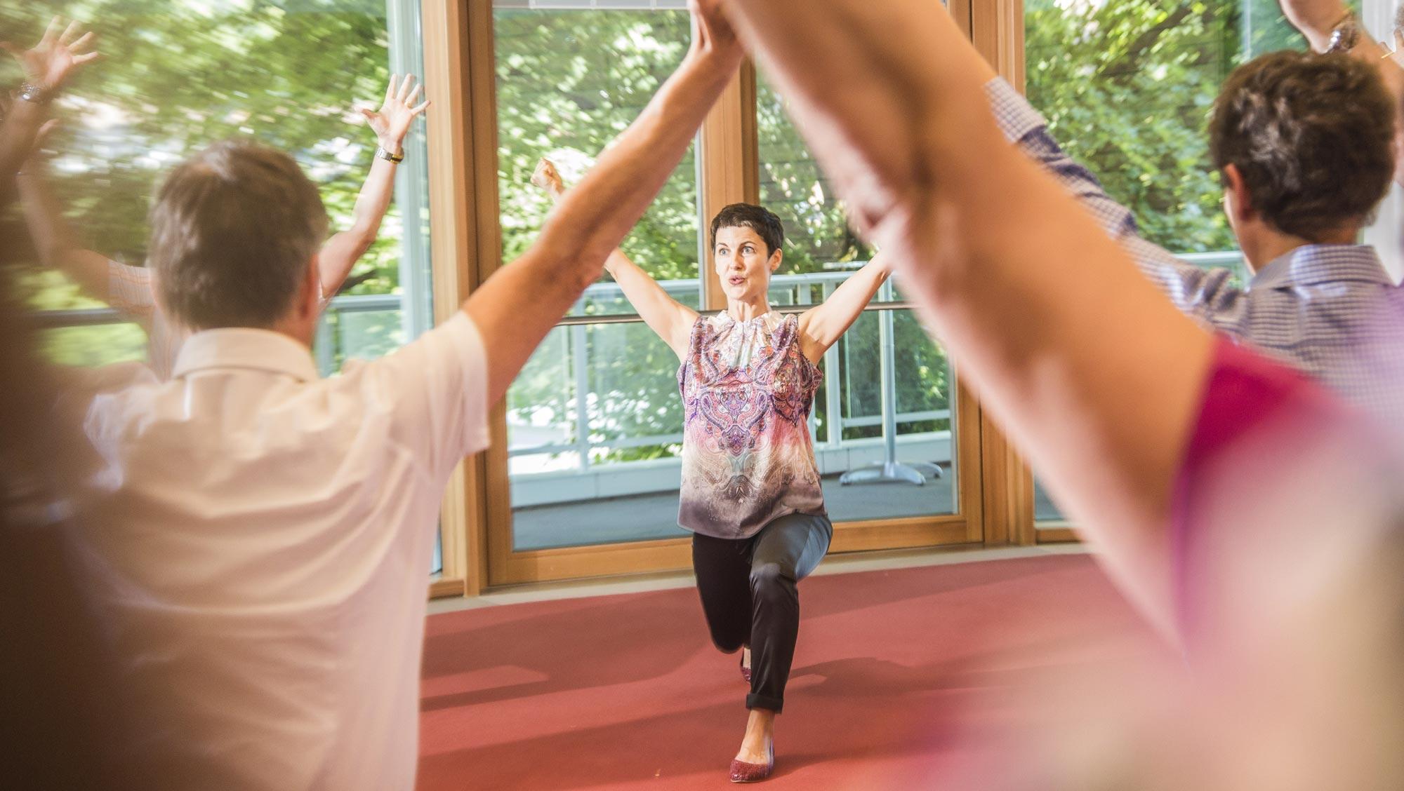 Yogalehrerin und Selfnessleiterin Kerstin Weinbrecht während einer Aktivpause mit Teilnehmenden eines Firmenevents
