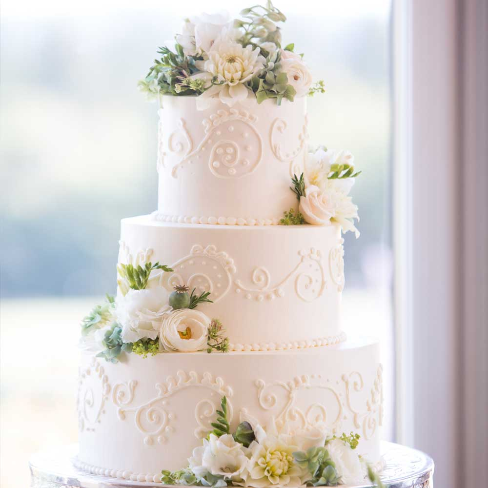 Dreistöckige weiße Hochzeitstorte mit Dekor und dezenter Blumendekoration