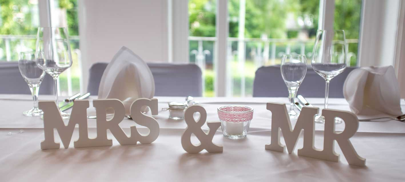 Tischdekoration bei einer Hochzeitsfeier mit großen Buchstabenaufstellern Mrs & Mr. Foto: Emotional Perspective