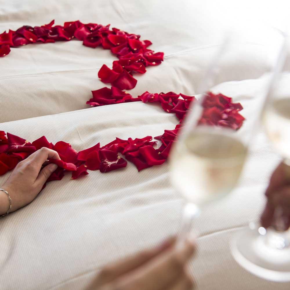 Mit Rosenblüten dekoriertes Bett in der Hochzeitssuite