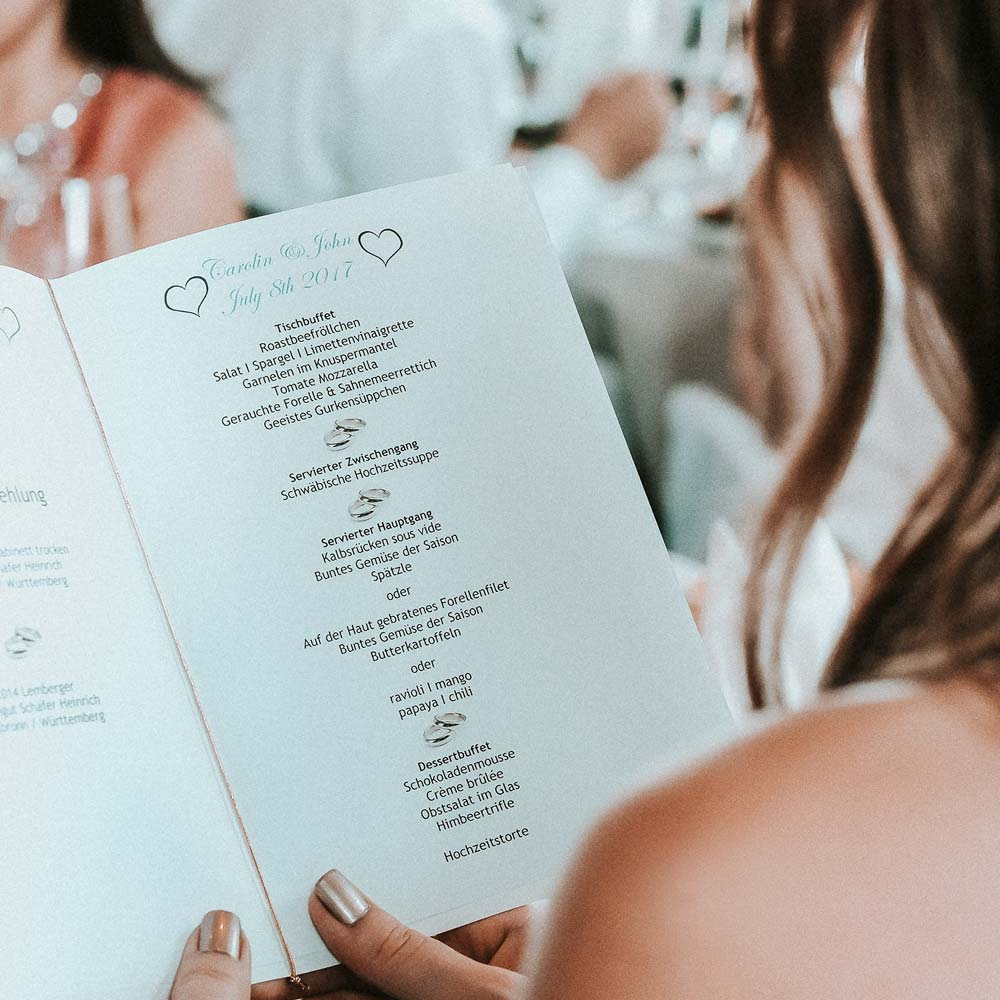 Braut mit Speisekarte zur Hochzeit mit Buffet und serviertem Menü