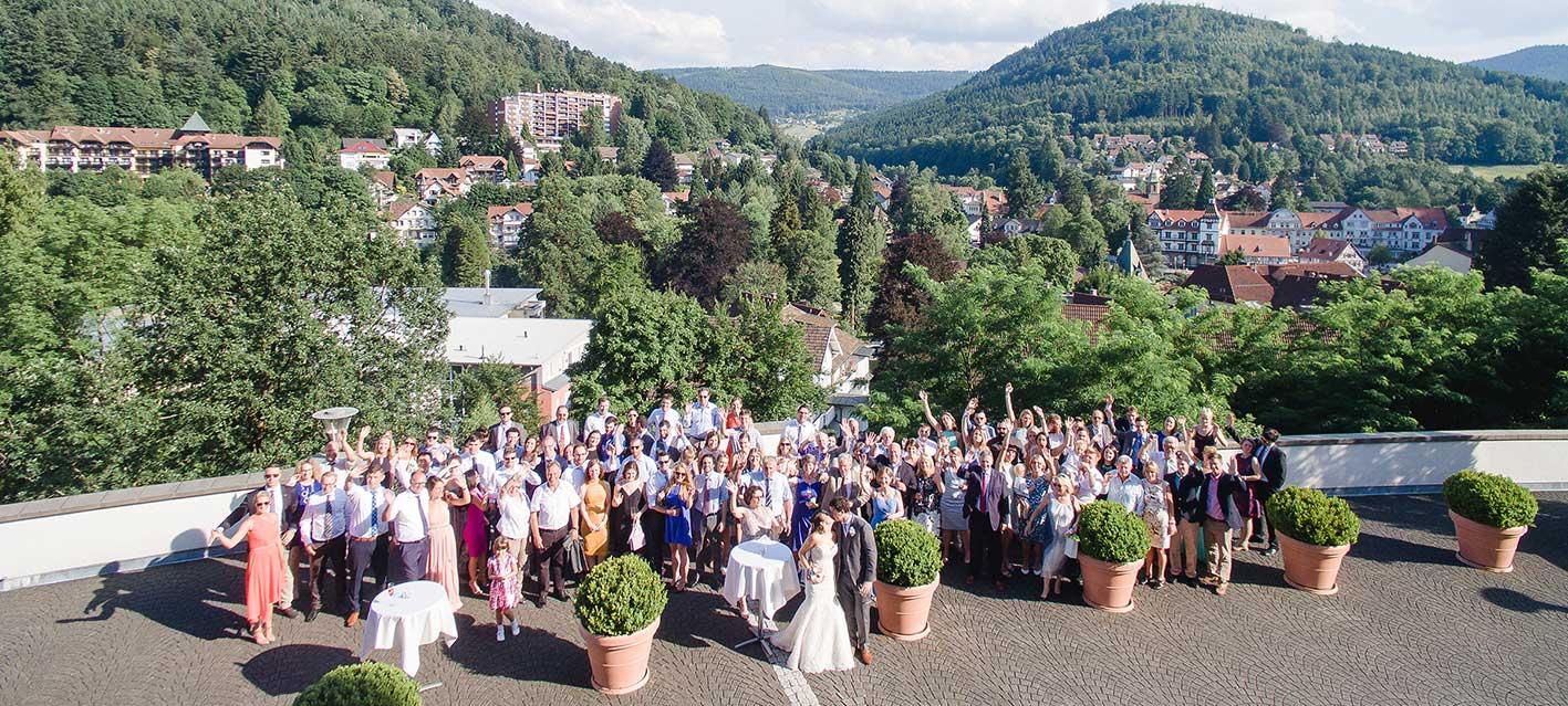 Brautpaar mit allen Gästen bei einer Hochzeit im Schwarzwald Panorama auf der Terrasse mit Ausblick auf Bad Herrenalb und die Natur. Foto: Emotional Perspective.