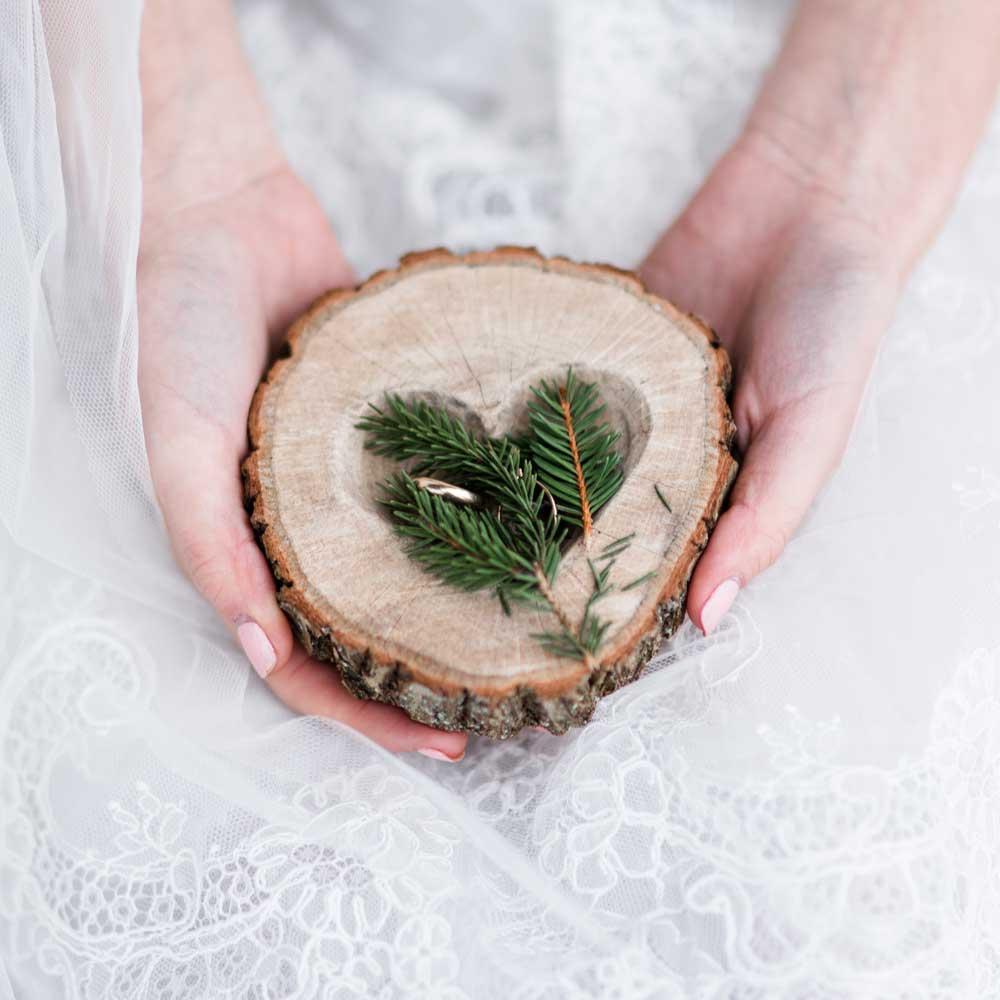 Braut hält eine Holzscheibe mit ausgeschnittenem Herz mit Zweigen und Eheringen in den Händen
