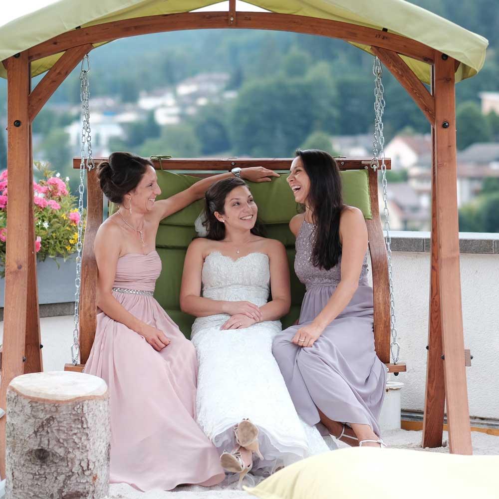 Braut sitzt mit zwei Brautjungfern auf einer großen Holzschaukel bei einer Hochzeit im Freien