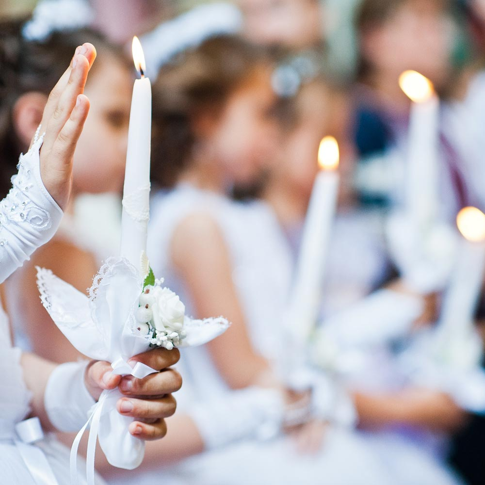 Kinder in weißen Kleidern mit Kerzen bei einer Kommunionfeier