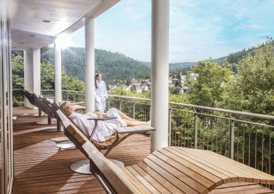 Zwei Frauen im Bademantel genießen auf einem Balkon mit Holterasse und Liegestühlen den Ausblick auf eine grüne Waldlandschaft im Hotel Schwarzwald Panorama