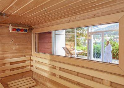 Eine Frau im Bademantel geht in eine Sauna im Hotel Schwarzwald Panorama, im Hintergrund ist eine Stadt und eine grüne Umgebung zu sehen