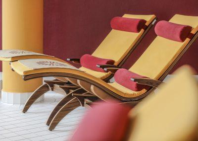 Holzliegestühle mit orangen und roten Polstern stehen im Spa und Wellness Bereich des Hotel Schwarzwald Panorama