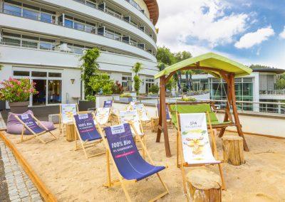 Auf einer Terasse ist eine Sandkasten aufgebaut, im Sandkasten stehen Liegestühle und andere Sitzmöglichkeiten. Im Hintergrund blauer Himmel und das Hotel Schwarzwald Panorama