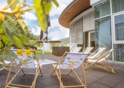 Auf einer Steinterrasse stehen Liegestühle vor grüner Kulisse im Hotel Schwarzwald Panorama