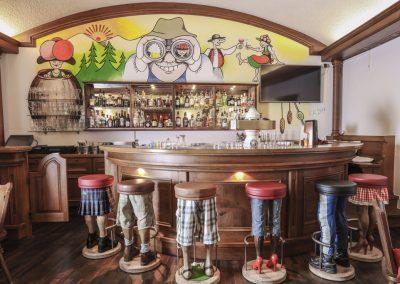 Vor einer Wand mit Cartoon Bemalung steht eine dunkelbraune Bar, mit Beinen als Barhocker.Die Schwarzwald Bar im Hotel Schwarzwald Panorama