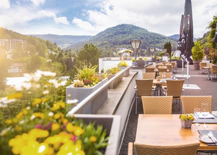 Auf einer Dachterasse stehen Tische und Stühle, im Hintergrund sieht man Wälder und die Andeutung einer Stadt, die Aussicht der Hotel Schwarzwald Panorama
