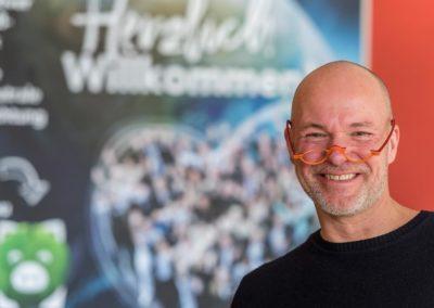 Stephan Bode steht lächelnd mit Brille am Hotelempfang. Er heißt die Gäste im Hotel SCHWARZWALD PANORAMA herzlich willkommen.