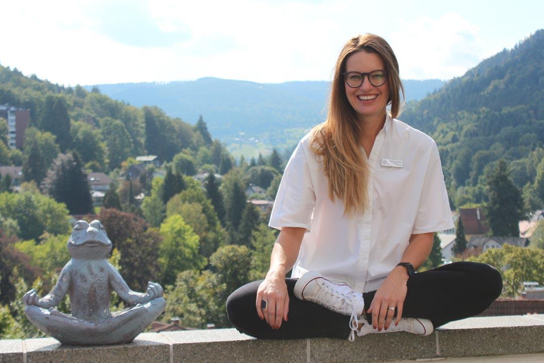 Alternativtext: Stephanie Schießl, zuständig für Entwicklung Nachhaltiges Bewusstsein & Nachhaltigkeit Hotellerie, sitzt auf einer Mauer vor der Aussicht des Hotel SCHWARZWALD PANORAMA