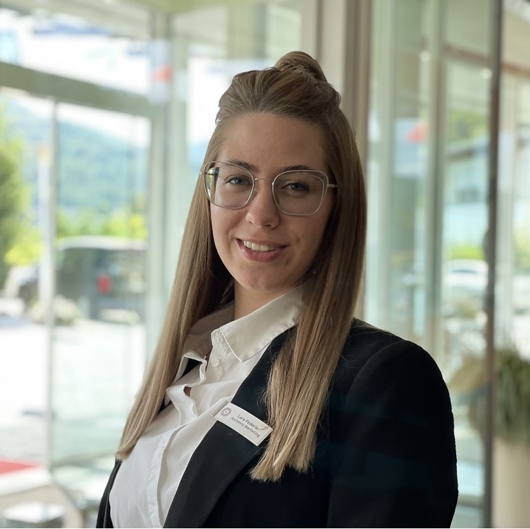 Mrs. Federle in front of an lighted window, she is marketing assistant in the Hotel Schwarzwald Panorama